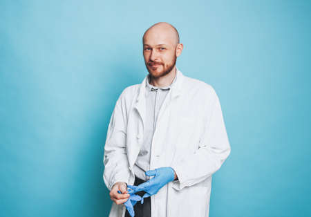 Attractive smiling man bald bearded doctor puts on rubber medical gloves looking at camera isolated on the blue background Stock Photo