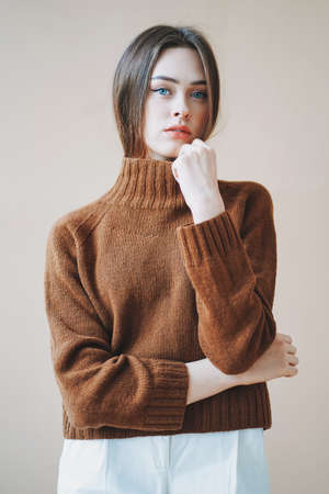 Young beautiful long brown-haired hair girl with blue eyes in brown knitted sweater looking at the camera on beige background