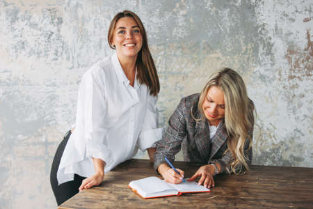 Young successful women colleagues discuss joint project at the table, coaching or mentoring