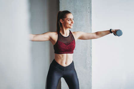 Attractive fit young woman in sport wear smiling girl trains with dumbbells at loft studio