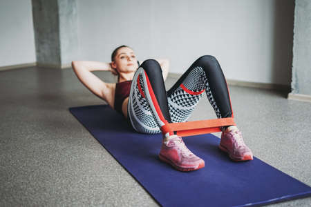 Attractive fit young woman sport wear fitness girl model doing stretching with elastic band doing sit-ups at loft studio workout class