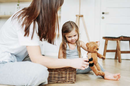 Cute toddler girl long fair hair big grey eyes wearing pajamas playing bear toy with mother at the room stay at home