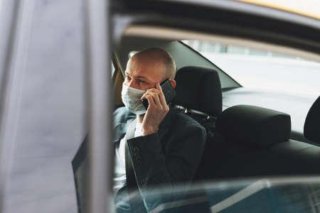Bald man businessman in medical face mask using mobile phone inside yellow car taxi. Concept of coronavirus quarantine