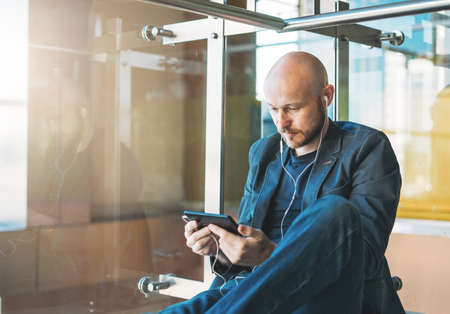 Handsome bald bearded man in suit using mobile phone at airport lounge