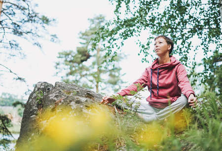Young smiling woman practice yoga outdoors in forest on the rocks. New normal social distance. Physical and mental health