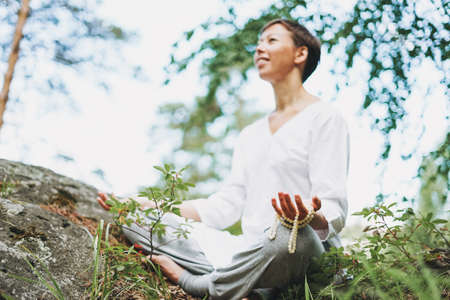 Young smiling woman with beads practice yoga outdoors in forest. New normal social distance. Physical and mental health
