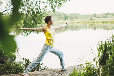 Young smiling woman practice yoga outdoors. New normal social distance. Physical and mental health