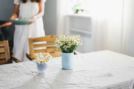 Table with flowers chamomile on linen tablecloth in living room, bright interior, Cottagecore Aesthetics