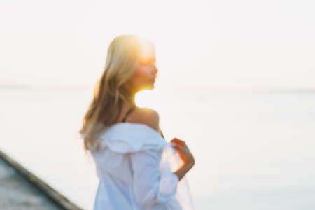 Beautiful blonde young woman in white shirt on pier on sunset. Blurred photo, background Imagens
