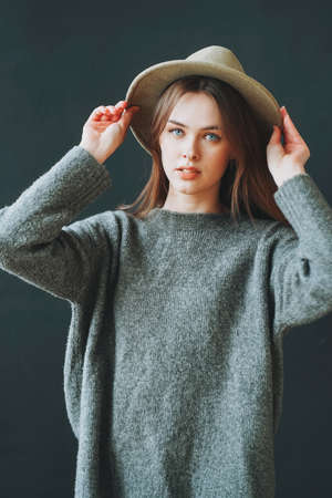 Young beautiful long brown-haired hair girl in felt hat and grey knitted sweater looking at the camera on dark background Фото со стока