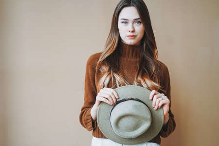 Young beautiful long brown-haired hair girl with blue eyes in felt hat and brown knitted sweater looking at camera on beige background Фото со стока