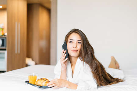 Beautiful young asian woman with long hair in white robe using mobile having breakfast growing and orange juice in bed of hotel room