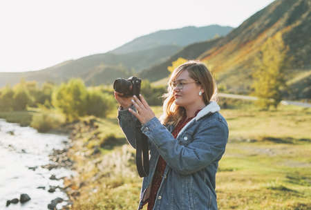Beautiful smiling blonde young woman traveler with photo camera in hands, trip to the mountains Stock Photo