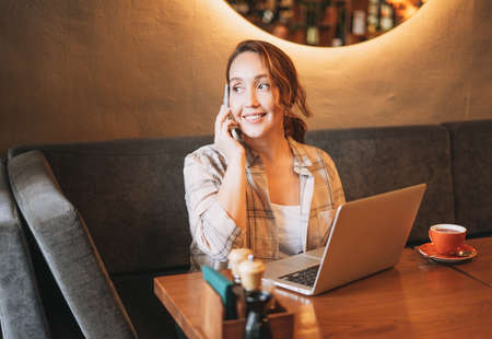 Adult charming brunette woman in plaid shirt working with laptop using mobile phone at cafe