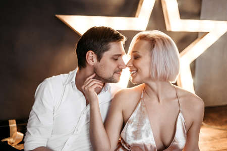 Beautiful happy couple young family in evening dresses kissing on dark bokeh background