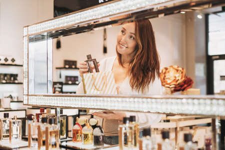 Adult pretty smiling woman with dark hair in cosmetics and perfume store, holiday shopping
