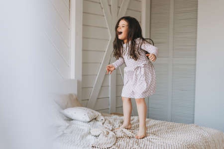 Cute long hair little girl jumping on parents bed at bright room, scandinavian interior