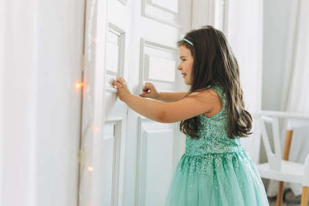 Cute long hair little girl jumping on parents bed at bright room, scandinavian interior Banco de Imagens