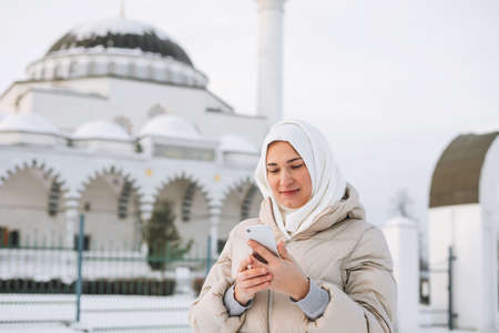 Beautiful smiling young Muslim woman in headscarf in light clothing using mobile in right-hand-drive car Banco de Imagens