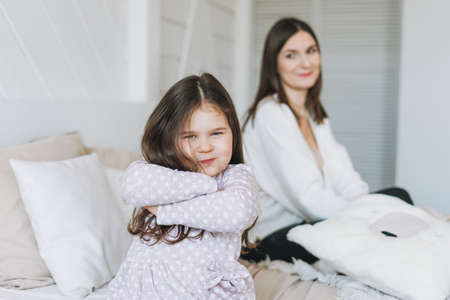 Cute long hair little girl helps dress her mother at bright bed room Banco de Imagens