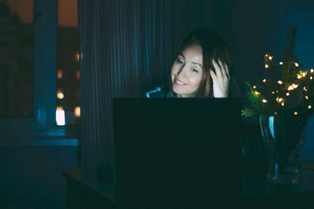 Attractive tired brunette woman middle age using laptop at home, working in night Banco de Imagens