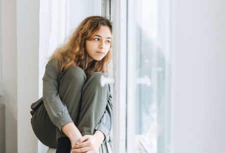 Beautiful sad unhappy teenager girl with curly hair sitting on window sill