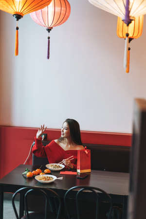 Beautiful smiling young asian woman in red with cup of tea restaurant through window