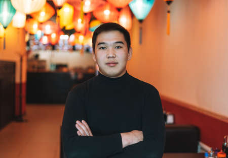 Handsome young asian man in black clothes in festive chinese vietnamese restaurant with colorful paper lanterns, small own business