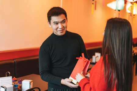 Beautiful young asian couple in red clothes give present in festive chinese vietnamese restaurant colorful paper lanterns, celebrating Chinese New Year Banco de Imagens