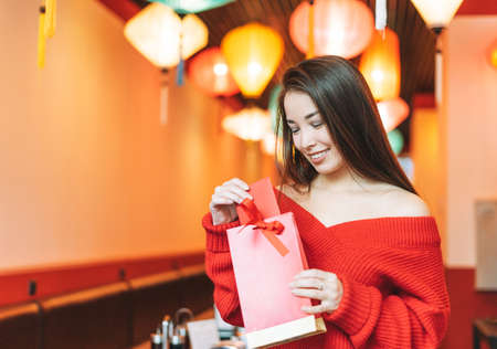 Beautiful smiling young asian woman in red clothes with gift bag with mandarins in cafe, celebrating Chinese New Year
