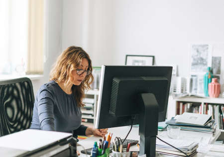 Charming adult woman middle aged with curly hair architect designer with color palette in hands in modern office working moment