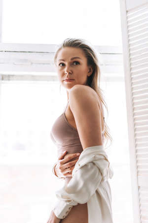Blonde sensual young woman 35 year plus with long hair in underwear and white shirt on window sill at bright interior
