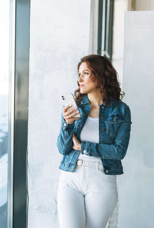 Charming young woman in jeans jacket using mobile phone in modern art gallery exhibition