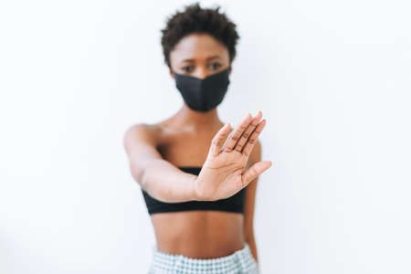 Beautiful young African American woman in black top and the face mask isolated on white background, stop virus concept