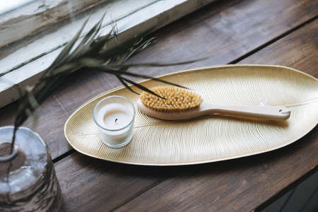 Bottle of shampoo, aromatic candle in glass and wooden brush with natural bristles on metal tray on wooden window sill, mockup