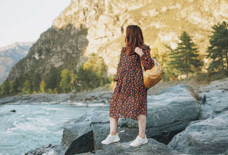 Young woman traveler in dress with backpack on mountain river on sunset Foto de archivo