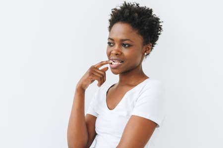 Portrait of charming smiling beautiful young African American woman in white t-shirt isolated on the white background