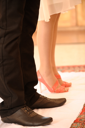 A young man in huge shoes and a girl in red shoes came to the Orthodox church to perform a wedding ceremony