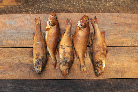 Medium-sized fish perch caught in a small river far from the city and plants, clogged with cherry sawdust