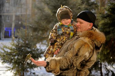 Отец и сын приходили в парк зимой, чтобы накормить синица и голубей Фото со стока