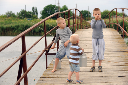 Three brothers came to the bridge in the village across the river to fish but instead ran along the bridge from the excess of feelings with a tourist aluminum kettle and small fish cans Stock Photo