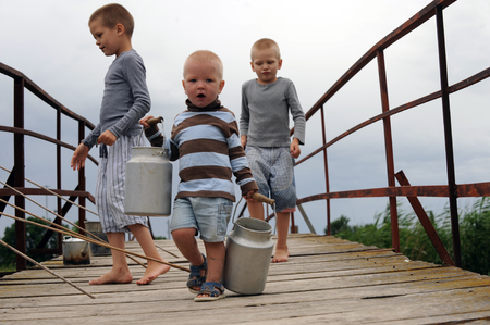Три брата пришли на мост в деревне через реку, чтобы ловить рыбу, но вместо этого бежали вдоль моста от избытка чувств с помощью туристического алюминиевого чайника и маленьких рыбных банок