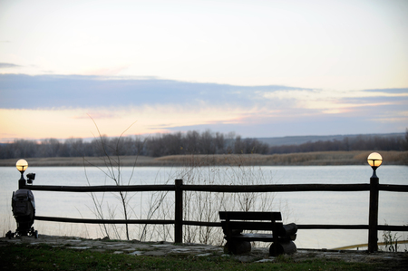 The bench and lanterns are a beautiful place for solitude over the river at sunset