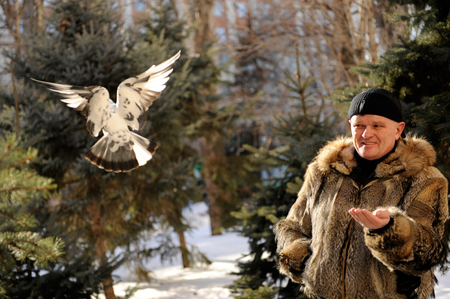 Father and son came to the park in the winter to feed titmouses and pigeons Фото со стока