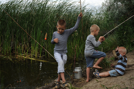 Three brothers gathered to fish on a fishing pole in a quiet backwater village lake