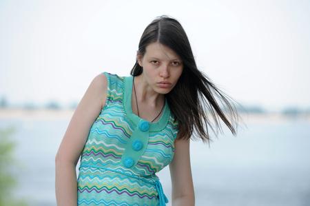 Довольно женщина из Волгограда на берегу великой русской реки Волги раздувает губы и показывает свои красивые волосы