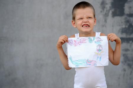 Старший мальчик в большой семье ходит в школу и показывает свои рисунки и школьный рюкзак