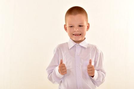Кавказский элементарный возраст мальчик в очках, создает в форме, изолированных на белом фоне. Концепция школы и образования.