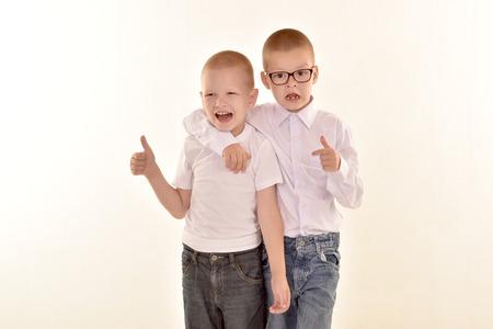 Кавказский элементарного возраста мальчик в очках, ставит в форме, изолированных на белом фоне с ним брат. Концепция школы и образования.