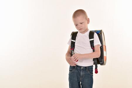 Кавказский элементарный возраст мальчик, ставит в форме и baccpack, изолированных на белом фоне. Концепция школы и образования. Фото со стока
